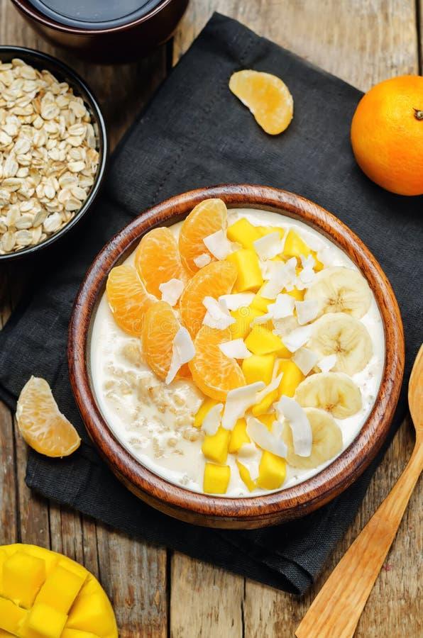 La farina d'avena con il mango, la banana, le arance del mandarino e la noce di cocco si sfalda immagine stock libera da diritti
