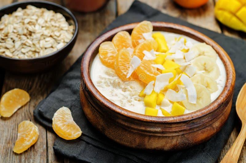 La farina d'avena con il mango, la banana, le arance del mandarino e la noce di cocco si sfalda fotografia stock libera da diritti