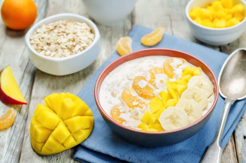 La farina d'avena con il mango, la banana, le arance del mandarino e la noce di cocco si sfalda immagini stock