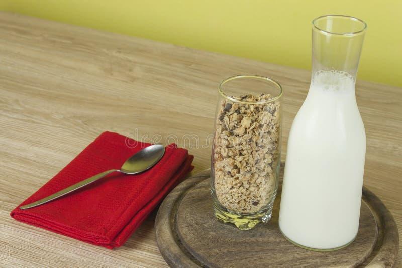 La farina d'avena si sfalda in un bicchiere accanto alla caraffa del latte Prima colazione sana con fibra immagini stock