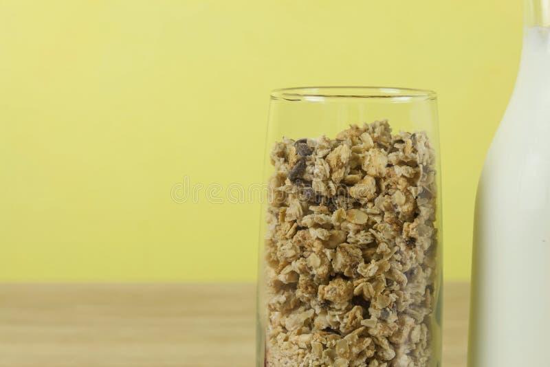 La farina d'avena si sfalda in un bicchiere accanto alla caraffa del latte Prima colazione sana con fibra fotografie stock libere da diritti
