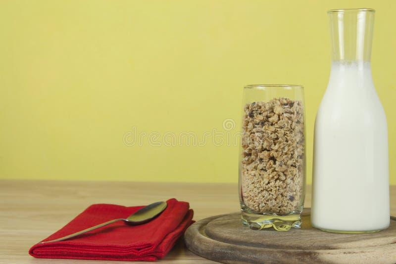La farina d'avena si sfalda in un bicchiere accanto alla caraffa del latte Prima colazione sana con fibra fotografia stock