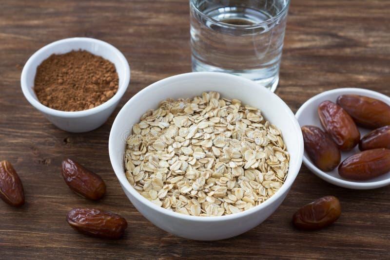 La farine d'avoine crue dans une cuvette blanche, date les fruits, le cacao et un verre de l'eau, ingrédients pour le petit déjeu photographie stock libre de droits
