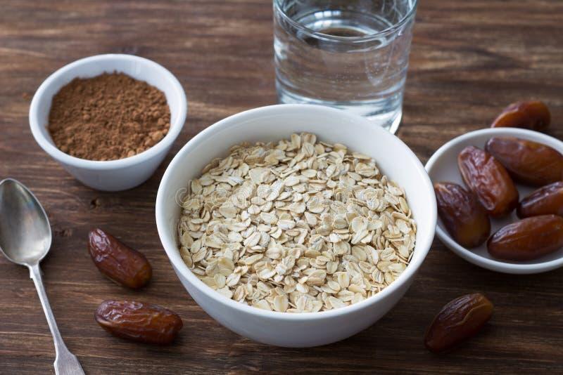 La farine d'avoine crue dans une cuvette blanche, date les fruits, le cacao et un verre de l'eau, ingr?dients pour le petit d?jeu photographie stock libre de droits