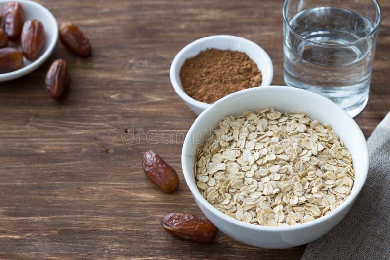 La farine d'avoine crue dans une cuvette blanche, date les fruits, le cacao et un verre de l'eau, ingr?dients pour le petit d?jeu photo libre de droits