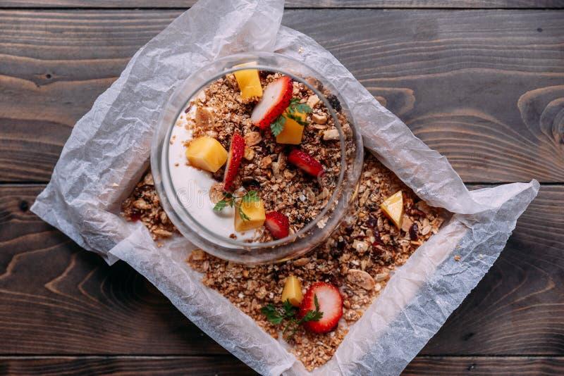 La farine d'avoine a servi dans la tasse en verre comprenant le yaourt à faible teneur en matière grasse, fraise fraîche et a déc images stock