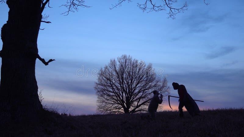 La faucheuse est venue pour une nouvelle victime et mène la victime à la mort Et l'homme prie pour la pitié Silhouette de coucher photos libres de droits