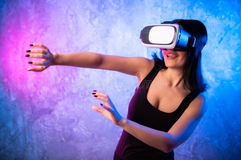 La favorable muchacha hermosa del videojugador que lleva las auriculares de la realidad virtual juega en el videojuego en línea,  foto de archivo