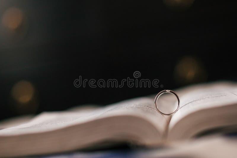 La fede nuziale si trova nella bibbia in espansione fotografia stock