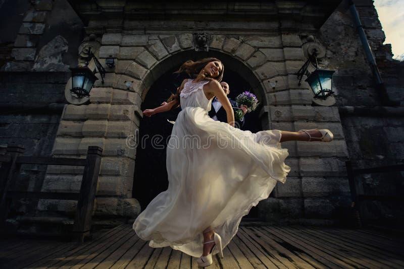 La felices novia y novio saltan feliz en el aire en el frente del imágenes de archivo libres de regalías
