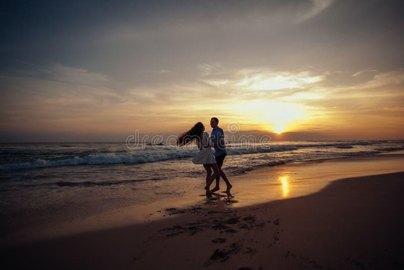 La felicidad y la escena romántica de los pares del amor partners en puesta del sol en la playa Amor goce Feliz imágenes de archivo libres de regalías