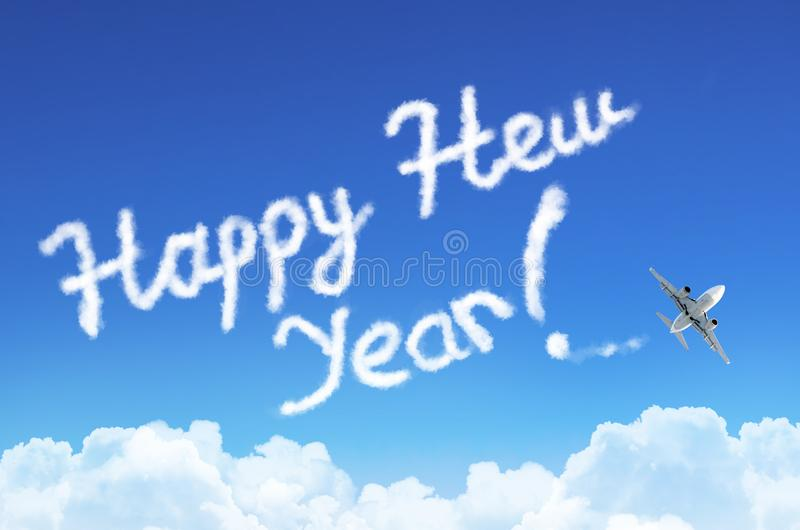 La Feliz Año Nuevo de la inscripción en el cielo de la nube y del vapor, aeroplano que vuela imagenes de archivo