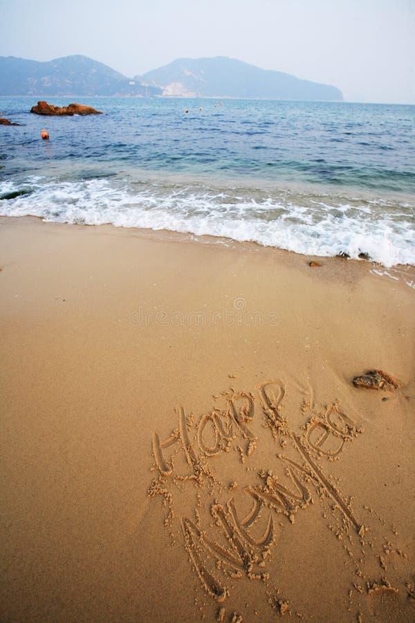 La Feliz Año Nuevo escribe en la playa imagenes de archivo