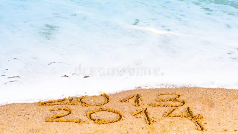 La Feliz Año Nuevo 2014 substituye el concepto 2013 en la playa del mar fotografía de archivo libre de regalías