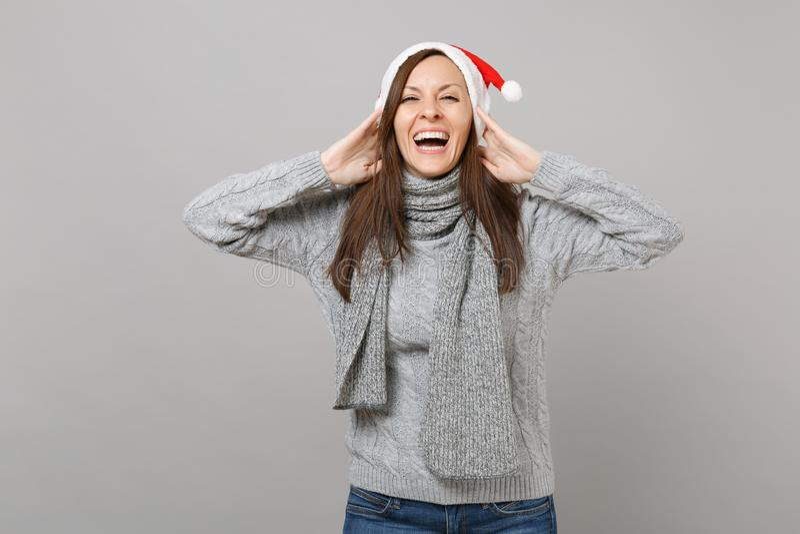 La feliz muchacha de risa de Papá Noel en sombrero gris de la Navidad de la bufanda del suéter puso las manos en la cabeza aislad imagenes de archivo