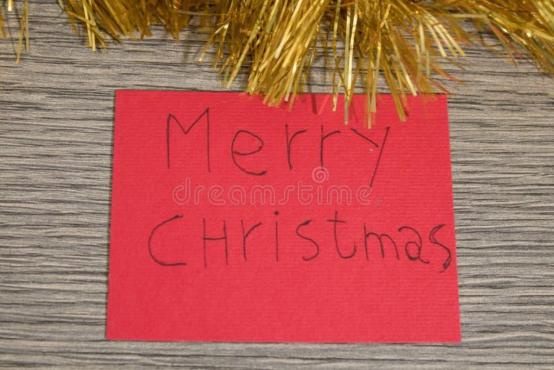 La Feliz Navidad escribe en un papel rojo con las decoraciones fotos de archivo libres de regalías
