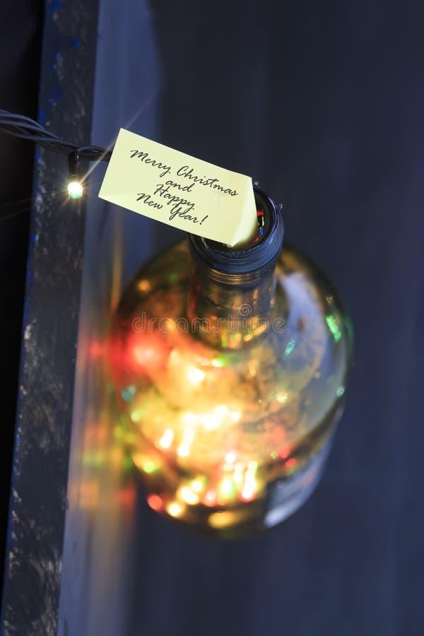 La Feliz Navidad y la Feliz Año Nuevo mandan un SMS, embotellan con las luces imagen de archivo libre de regalías