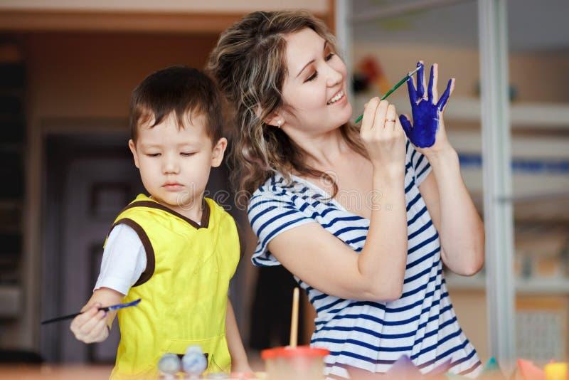 La feliz niñez, niño pequeño que juega con su madre, dibuja, las pinturas en las palmas imagenes de archivo
