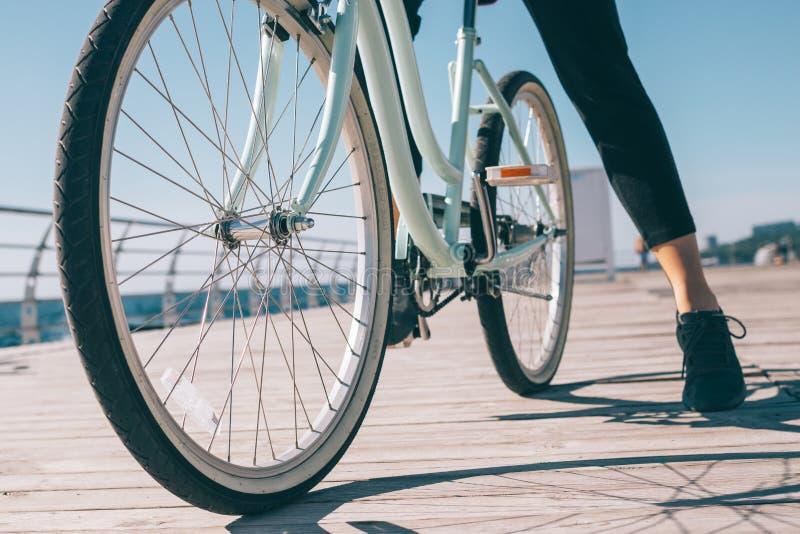 La femelle élégante s'est arrêtée pendant un tour de vélo sur le bord de la mer images stock