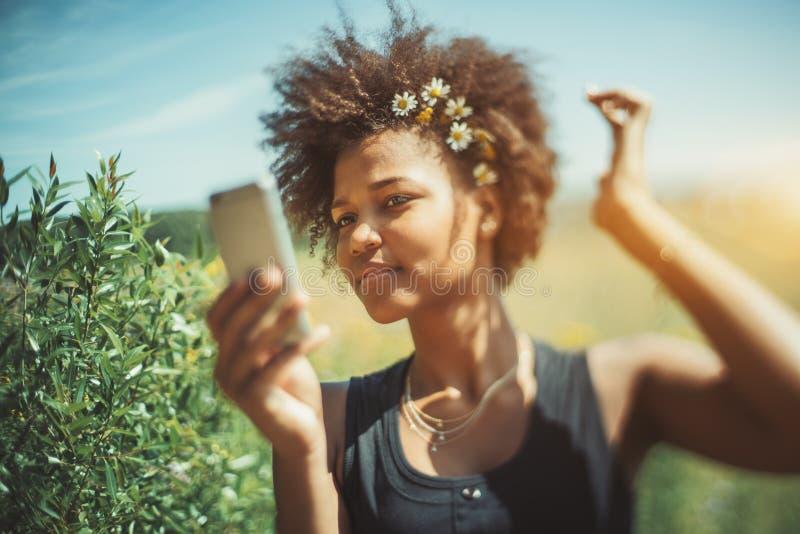 La femelle adolescente bouclée noire fait le selfie photo stock