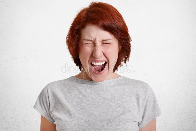 La femelle agressive désolée avec les cheveux roux crie désespérément, a l'expression du visage de mécontentement, exprime l'agre photo libre de droits