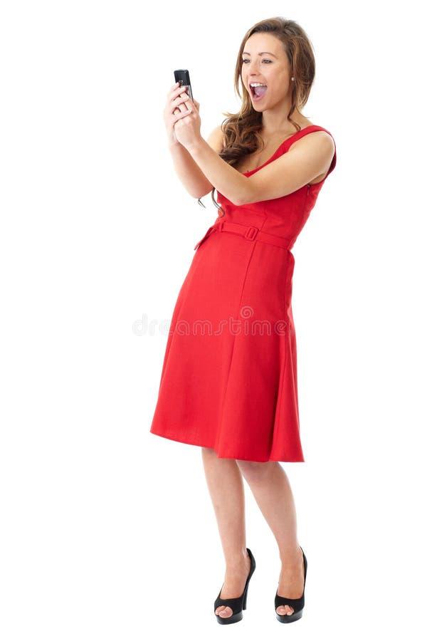 La femelle attirante heureuse dans la robe rouge prend des photos photographie stock libre de droits