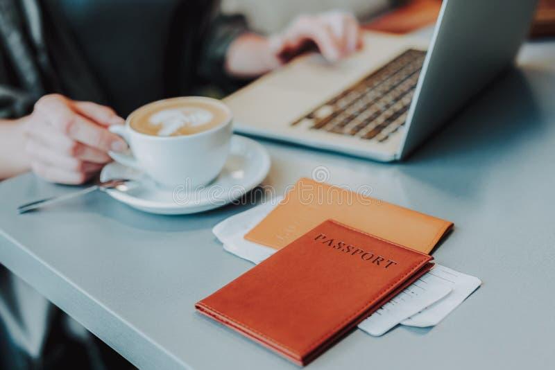 La femelle avec l'ordinateur portable et les documents apprécie le café dans le restaurant photographie stock libre de droits