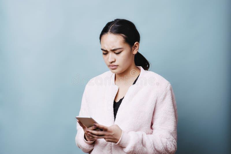La femelle de l'adolescence réagit dans la colère sur son service de mini-messages de téléphone portable photographie stock libre de droits