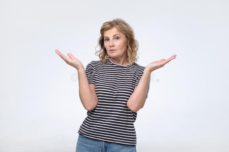 La femelle habillée en passant dans la confusion, gesticule des épaules de même que ne connaît pas la réponse photos libres de droits