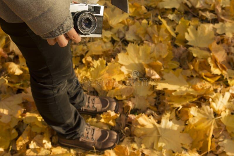 La femelle jaune tenant rétro †d'appareil-photo «part au sol, saison d'automne photo libre de droits