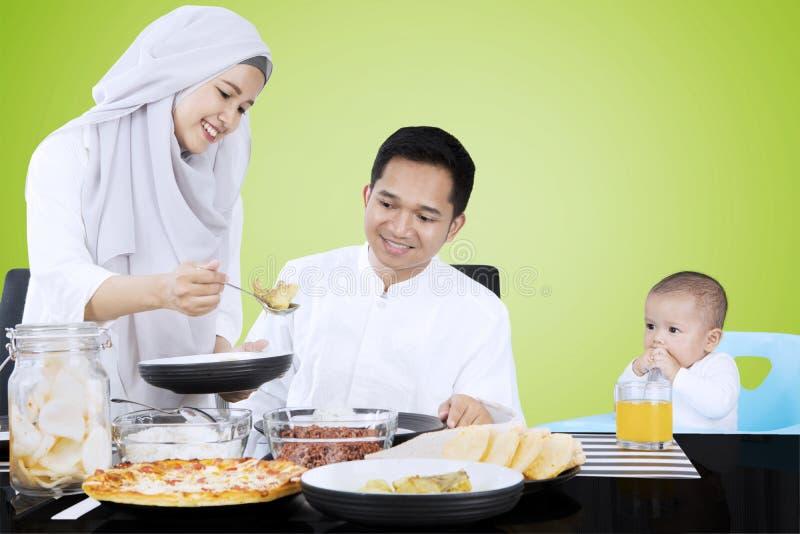 La femelle musulmane sert la nourriture pour la famille images libres de droits