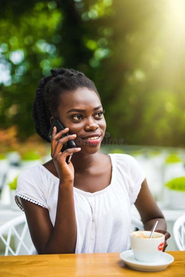 La femelle pelée foncée attirante a la conversation téléphonique en café extérieur, apprécie le gâteau et le cappuccino savoureux images stock