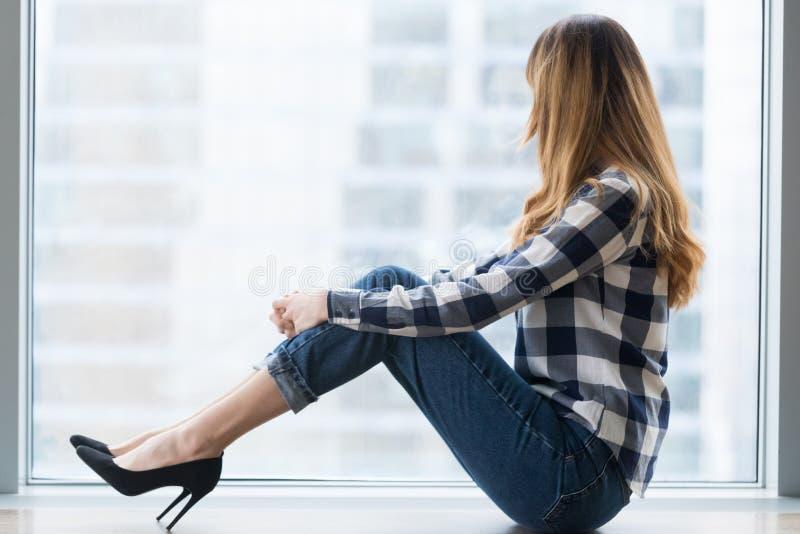 La femelle réfléchie s'asseyent sur le rebord de fenêtre rêvant de l'avenir photo stock
