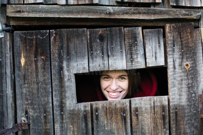 La femelle regarde la petite fenêtre dans le hangar en bois photo stock