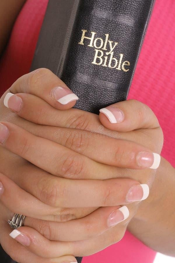 La femelle remet la bible de fixation photo stock