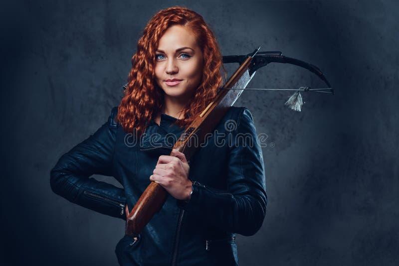 La femelle rousse tient l'arbalète photo libre de droits