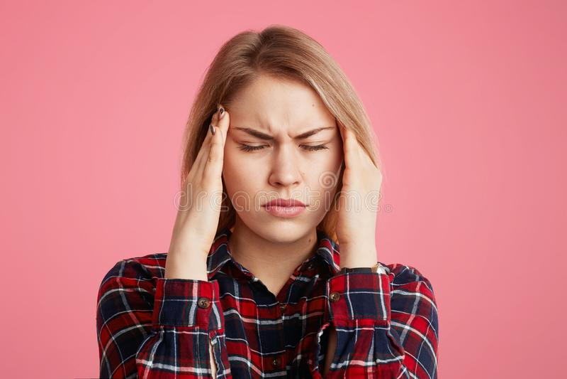 La femelle stressante déprimée a le mal de tête, garde des mains sur des temples, ferme des yeux comme douleur terrible de sentir images stock