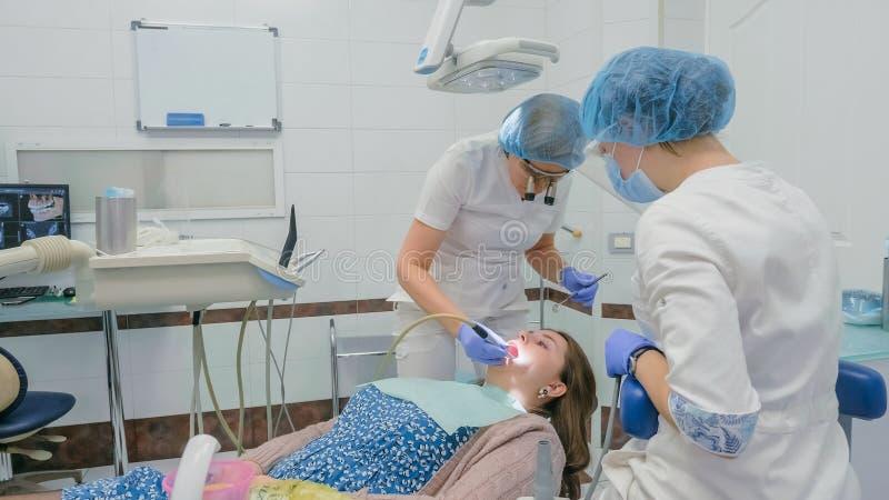 La femme à la clinique de dentiste obtient le traitement dentaire pour remplir cavité dans une dent Restauration et matériau comp photographie stock libre de droits