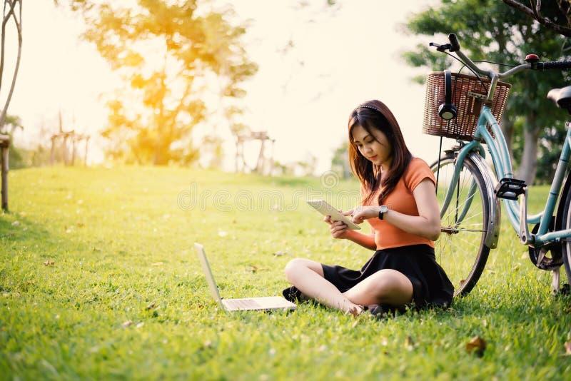 La femme à l'aide du comprimé et de l'ordinateur portable dans le parc, concept extérieur, détendent le concept, concept de techn image libre de droits