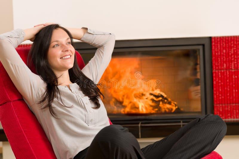 La femme à la maison de cheminée de l'hiver détendent le fauteuil rouge images libres de droits