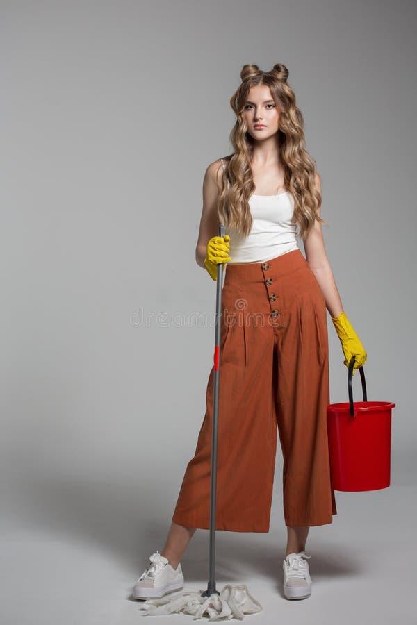 La femme à la mode avec de longs cheveux tient à disposition un seau rouge images libres de droits