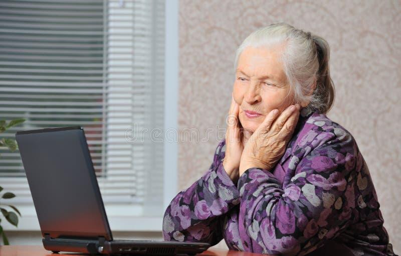 La femme âgée devant l'ordinateur portatif images stock