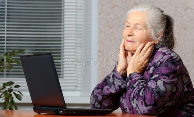 La femme âgée devant l'ordinateur portatif image libre de droits