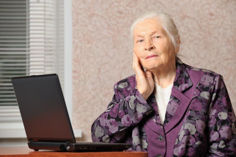 La femme âgée devant l'ordinateur portatif photographie stock libre de droits