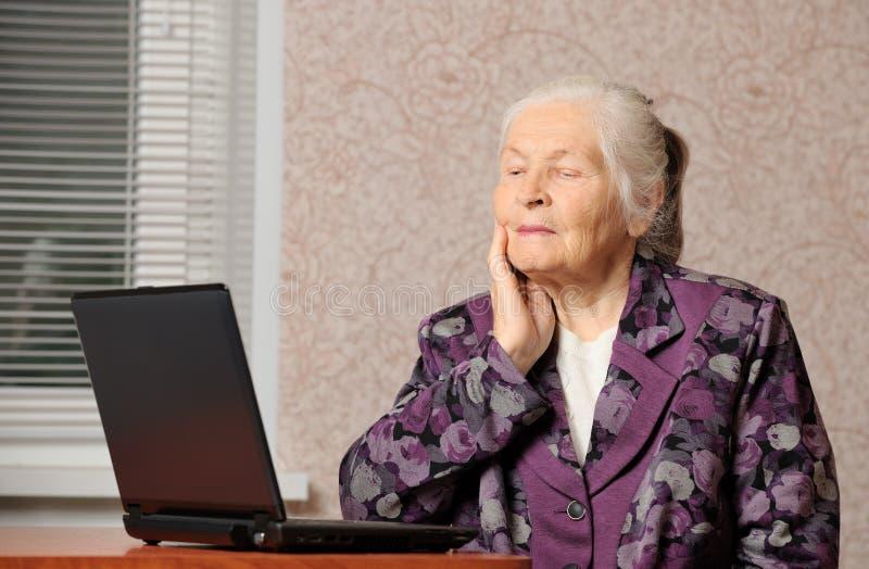 La femme âgée devant l'ordinateur portatif images libres de droits