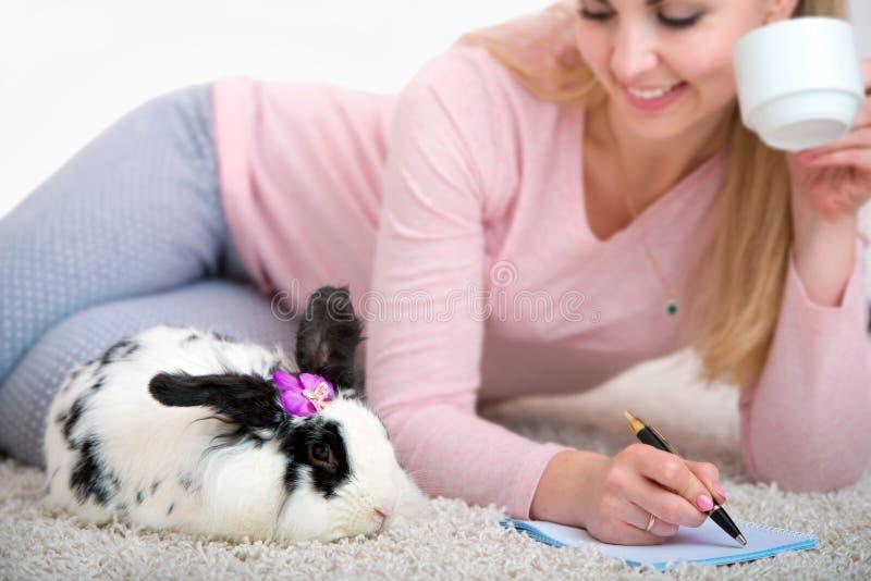 La femme écrit une lettre dans une atmosphère à la maison romantique, se trouvant sur le tapis avec un lapin images libres de droits