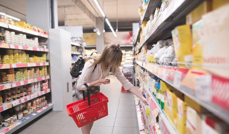 La femme élégante avec un panier rouge dans des ses mains choisit une céréale dans un supermarché image stock