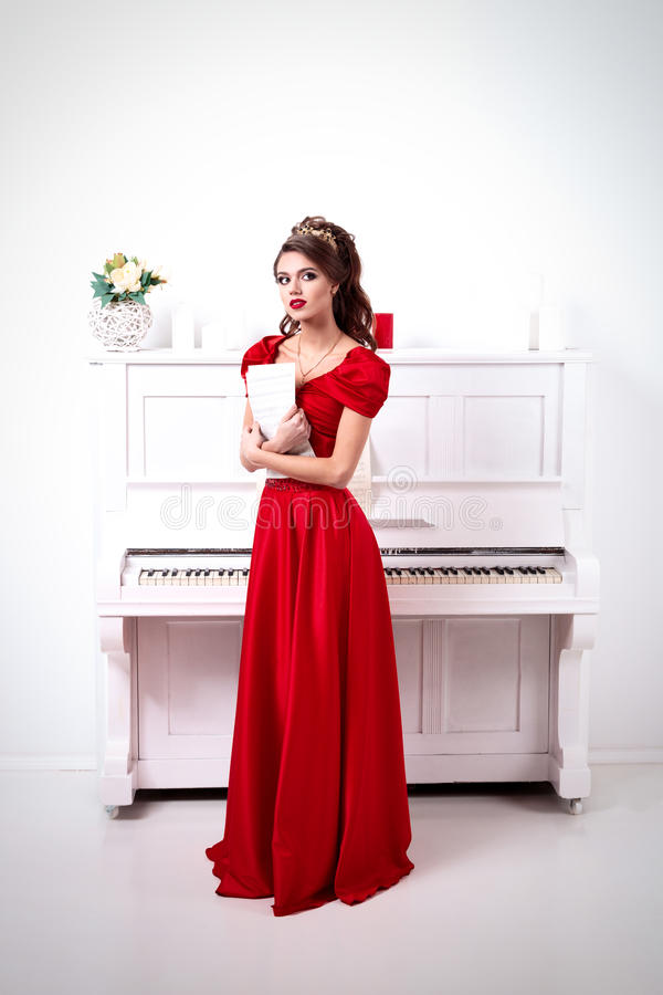 La femme élégante dans une longue robe rouge tient les notes non reconnues, stan photos libres de droits
