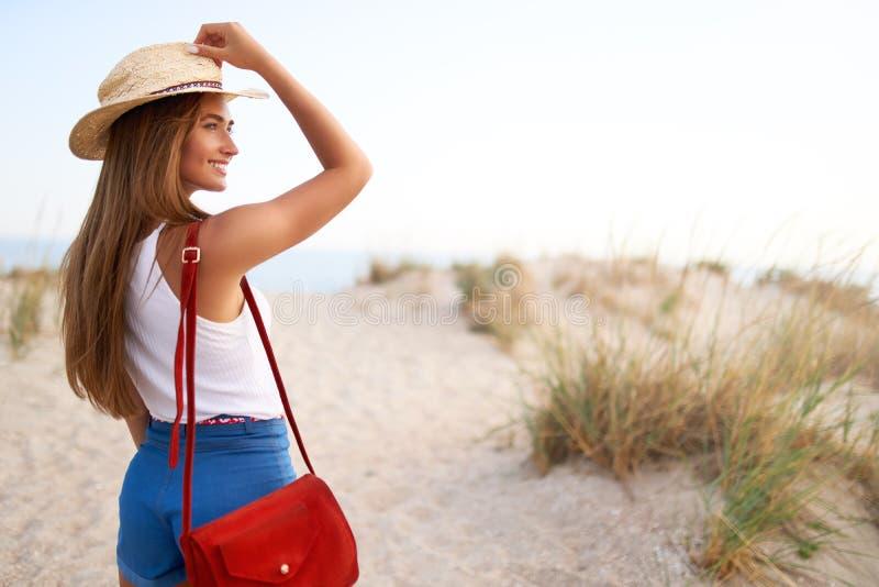 La femme élégante marche à la plage dans le chapeau de paille, les shorts de denim d'été et le sac à la mode rouge Femelle bronzé photo libre de droits