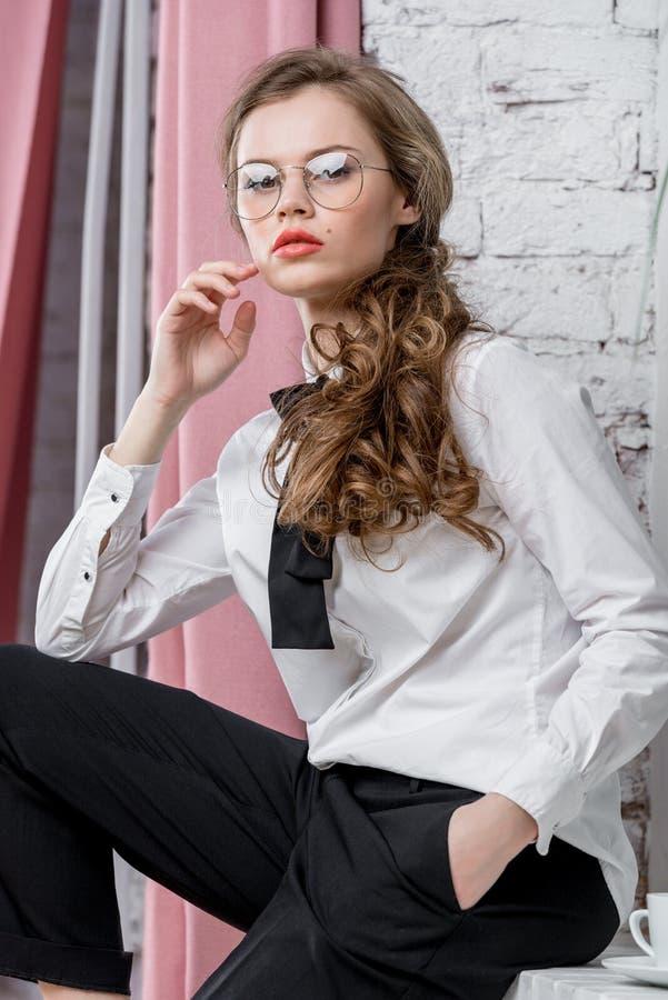 La femme élégante posant avec des verres dans les affaires vêtx photo libre de droits